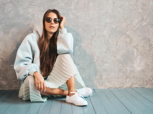 若い美しい笑顔の女性は、ピースサインを示しています。カジュアルな夏のパーカーとスカートの服でトレンディな女の子。床に座って