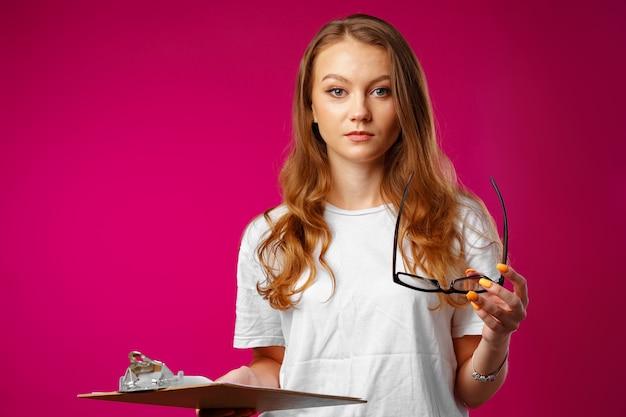 Молодая красивая улыбающаяся женщина, стоящая и держащая буфер обмена на розовом фоне