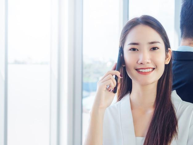 携帯電話で話し、巨大なガラス窓にスーツを着たビジネスマンと立っている若い美しい笑顔の女性
