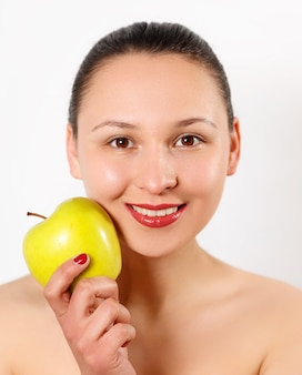 Young beautiful smiling woman touches the apple to face.