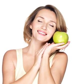 若い美しい笑顔の女性は、白で隔離された顔にリンゴに触れます。