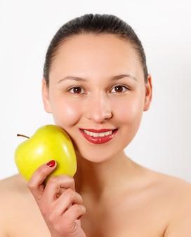 젊은 아름 다운 웃는 여자 얼굴에 사과를 건 드리면.