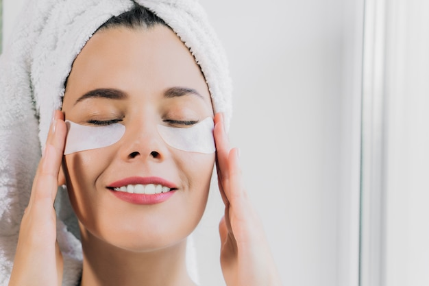 Young beautiful smiling woman in white towel and robe with eye patches and closed eyes