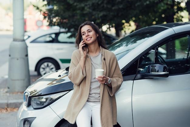 커피 한 잔을 들고 웃고 있는 젊고 아름다운 여성은 전기 자동차 근처에서 스마트폰으로 말한다
