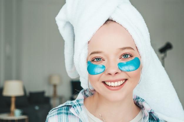 Giovane bella donna sorridente con macchie sotto gli occhi
