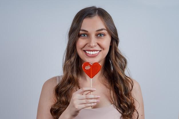 赤いハートのお菓子と若い美しい笑顔の女性。