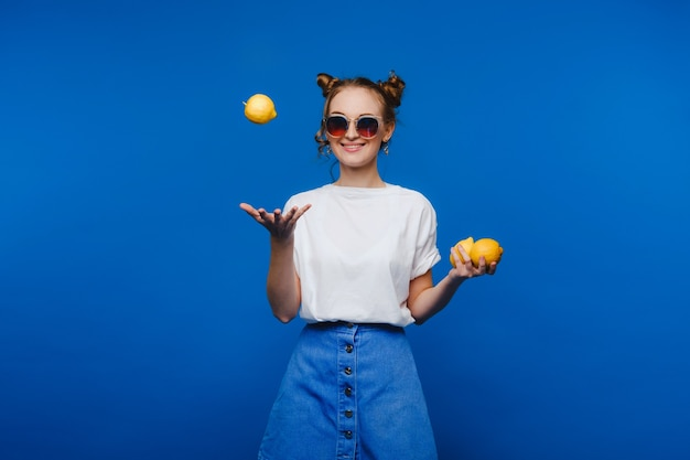Young beautiful smiling women with curly hair tasting sour lemon halves emotionally. funny girl with wavy hairstyle and bright make up isolated over yellow background. copy space. yellow lifestyle
