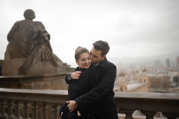 愛の若い美しいスペインカップルがカタルーニャ国立美術館の前で雨の中で抱きしめます。バルセロナのスペイン広場を背景に撮影します。