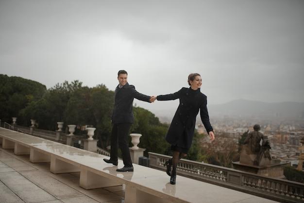 愛の若い美しいスペインカップルがカタルーニャ国立美術館の前で雨の中で抱きしめます。バルセロナのスペイン広場で撮影。