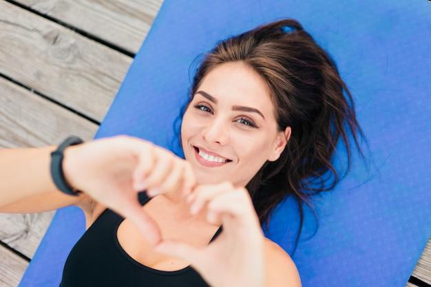 Молодая красивая спортивная женщина лежит на циновке и показывает руками символ сердца.