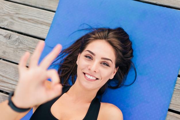 Молодая красивая спортивная женщина лежит на циновке и показывает символ ок.