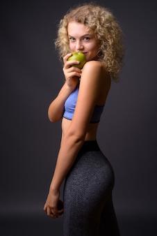 Молодая красивая спортивная женщина готова к тренажерному залу, держа здоровое яблоко