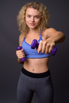 Young beautiful sport woman ready for gym holding dumbbells