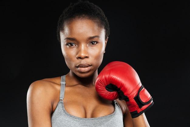 黒い壁に分離されたボクシンググローブと立っている若い美しいスポーツ女性