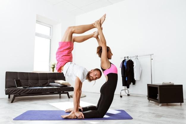 若い美しい陽気なカップルが自宅でパートナーのヨガのアーサナを練習します。
