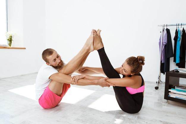 若い美しい陽気なカップルが自宅でヨガのアーサナを練習します。ナバサナ。