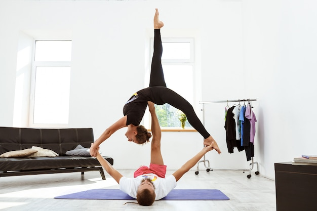 Young beautiful sportive couple practicing yoga asanas at home.