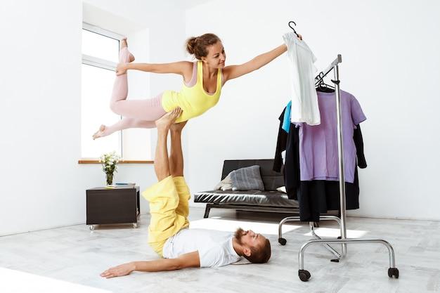 Молодые красивые спортивные пары обучения партнер асаны йоги дома.