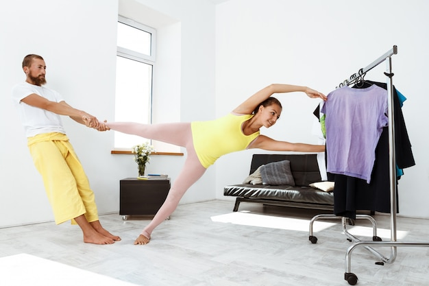 Young beautiful sportive couple training partner yoga asanas at home.