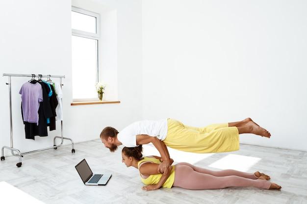 Young beautiful sportive couple training partner yoga asanas at home.