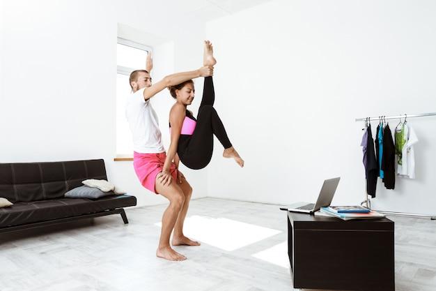 若い美しい陽気なカップル自宅でヨガのアーサナをトレーニングします。