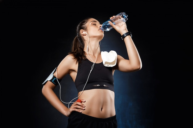 Young beautiful sportive girl drinking water over dark wall.