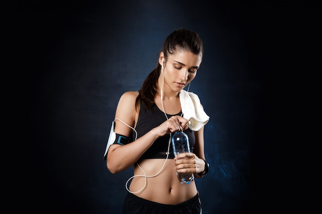 Young beautiful sportive girl holding water over dark wall.