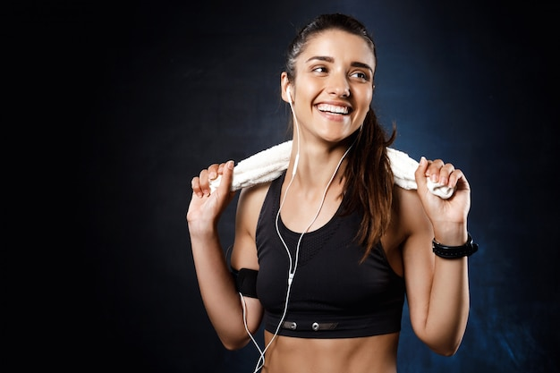 Young beautiful sportive girl listening music over dark wall.