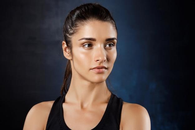Young beautiful sportive girl posing over dark wall.