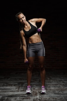 Young beautiful sportive girl smiling, training over dark wall