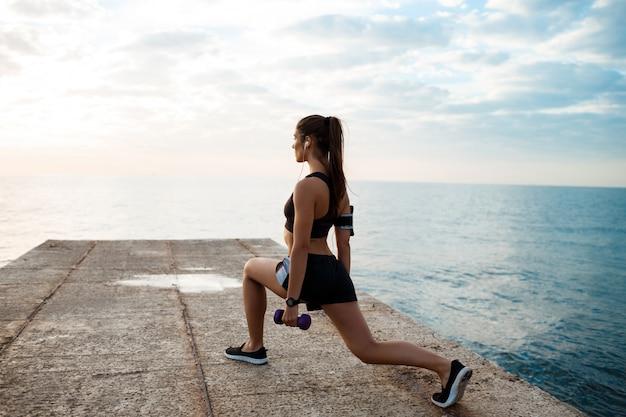 Молодая красивая спортивная девушка обучение на рассвете над моря.