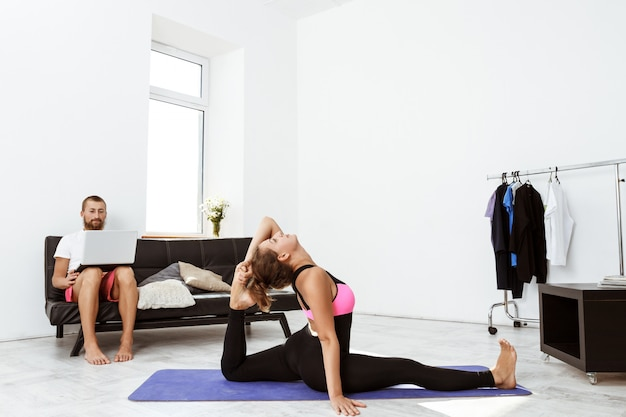 Giovani bei asana allegri di yoga di addestramento della ragazza a casa.