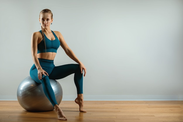 The young, beautiful, sports girl doing exercises on a fitball at the gym on gray space