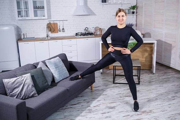 레깅스와 상의를 입은 젊고 아름다운 스포츠 소녀는 집에서 소파에서 운동을 합니다. 건강한 생활. 여자는 집에서 운동하러 간다.