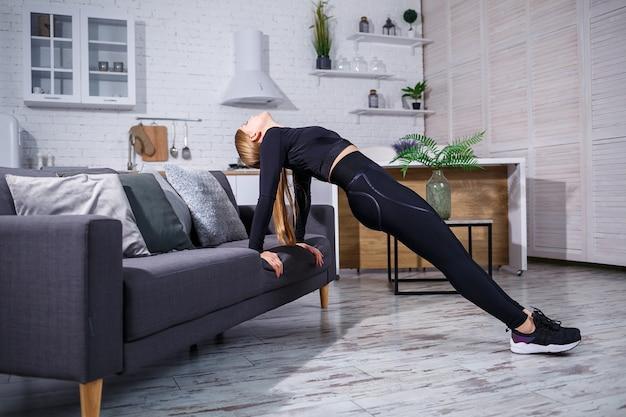 Молодая красивая спортивная девушка в леггинсах и топе делает упражнения дома на диване. здоровый образ жизни. женщина занимается спортом дома.