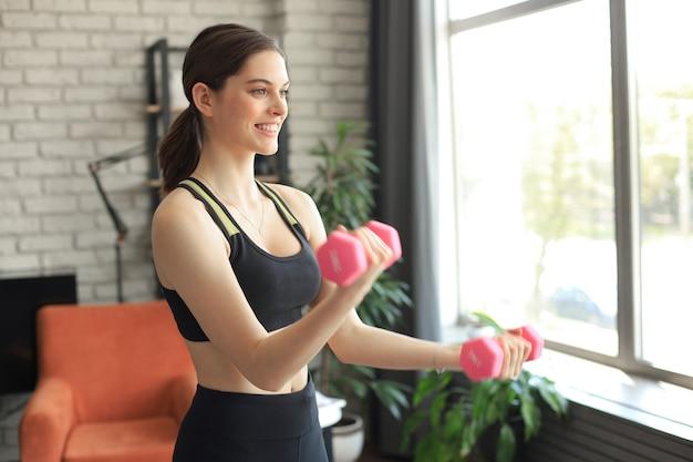 レギンスとトップの若い美しいスポーツの女の子は、ダンベルでエクササイズをします。健康的な生活様式。女性は家でスポーツに行きます。