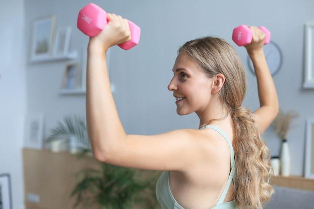 레깅스와 상의를 입은 젊고 아름다운 스포츠 소녀는 아령으로 운동을 합니다. 건강한 생활. 여자는 집에서 운동하러 간다.