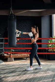Young beautiful sports girl in sportswear and boxing gloves hits a punching bag in modern black gym.