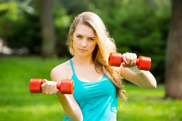 緑の芝生の背景に公園でダンベルを持つ若い美しいスポーツの女の子