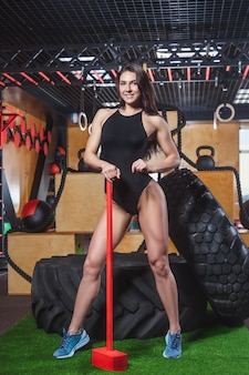 Young beautiful sports a slender girl in a black bathing suit holding a red hammer.