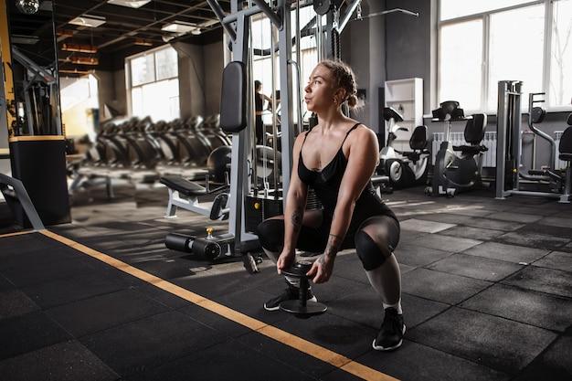 Молодая красивая спортивная женщина сидит на корточках с тяжелыми гантелями в тренажерном зале