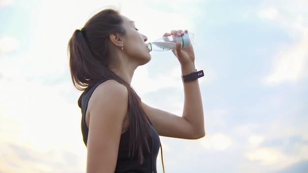 젊고 아름다운 운동가는 훈련 후 야외에서 병에서 물을 마신다