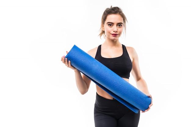Young beautiful sportswoman practicing yoga on blue mat.
