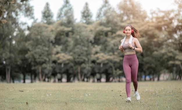 コピースペース、日光の下で公園で走っているヘッドフォンで若い美しいスポーツウーマン。