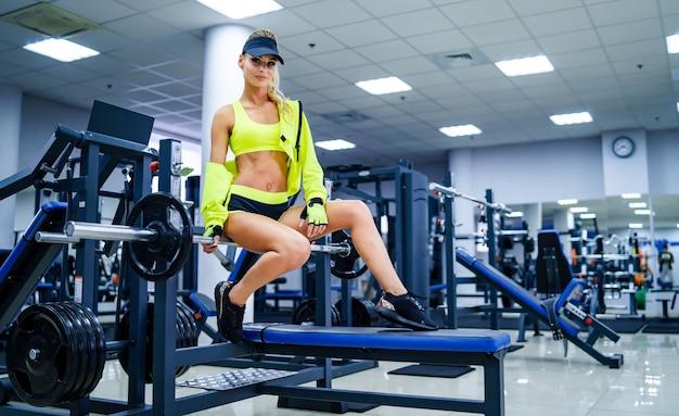素敵な体を持つ若い美しいスポーツウーマン。スポーツ用品でポーズをとる金髪のフィットネスの女の子。ジムの背景。明るいスポットウェア。ジムの背景。