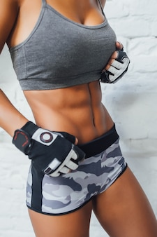 Young beautiful sporty girl in the gym, close up picture of strong stomach