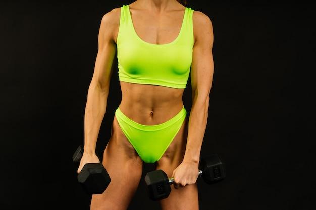 若い美しいスポーティな筋肉の女性、スタジオで白と黒の背景に対して分離