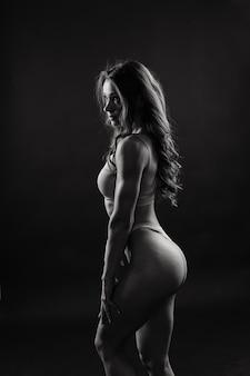 白と黒の背景に対して分離された若い美しいスポーティな筋肉の女性