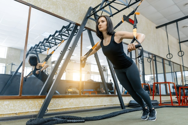 Young beautiful sporty woman exercising on fitness straps system