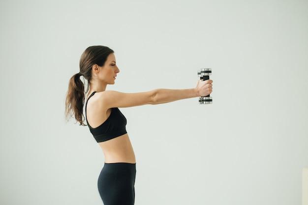 スポーツトレーニングをしている若い美しいスポーティな女性の家。スタジオショット。